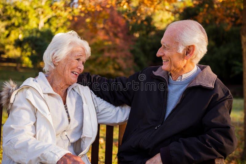 Höga par som omfamnar på en bänk royaltyfri foto