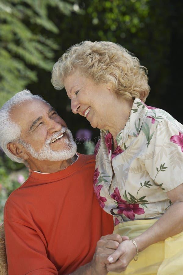Höga par som omfamnar på trädgården arkivbild