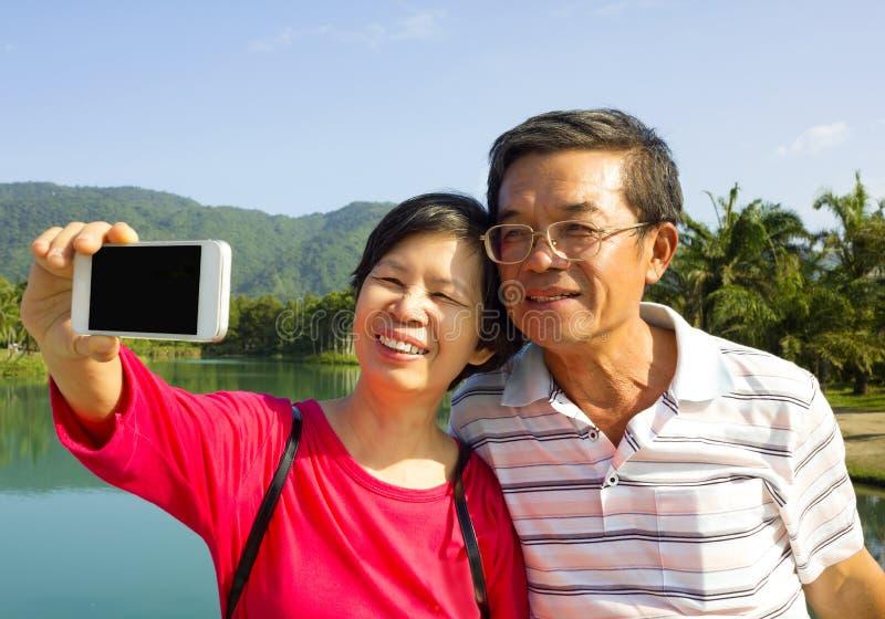 Höga par som på egen hand tar bilden i yttersida royaltyfri foto