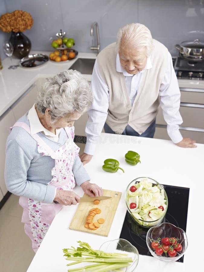 Höga par som pratar i kök fotografering för bildbyråer