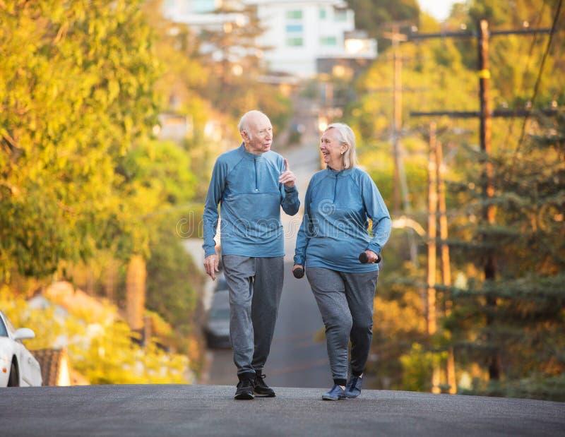 Höga par som promenerar gatan på kullen royaltyfri foto