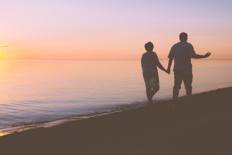Höga par som promenerar stranden royaltyfria bilder