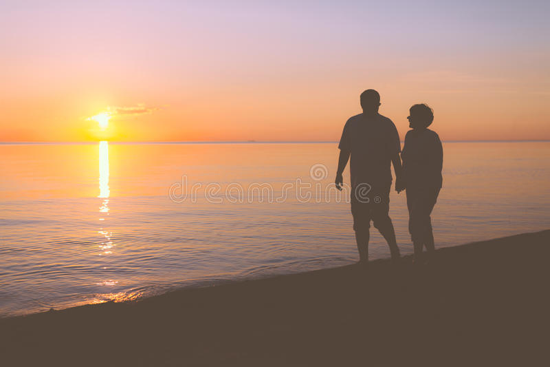 Höga par som promenerar stranden arkivbild