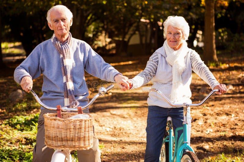 Höga par som rider deras cykel och innehav deras händer arkivbild