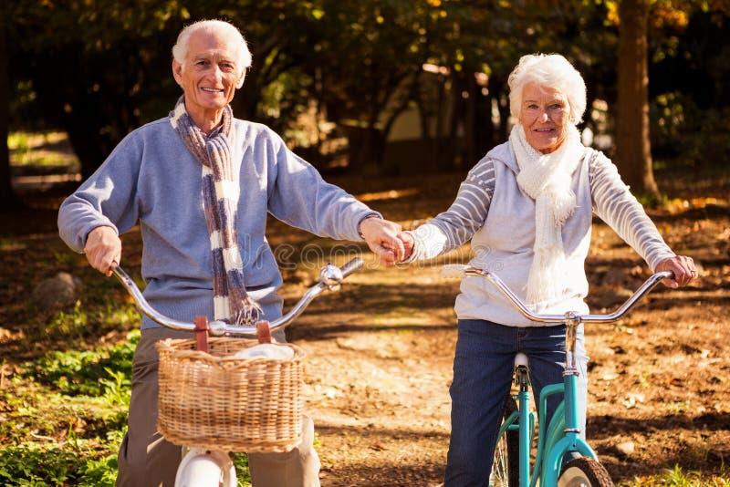 Höga par som rider deras cykel och innehav deras händer royaltyfri bild