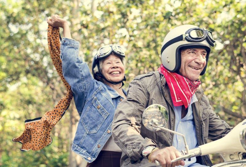 Höga par som rider en klassisk sparkcykel arkivfoton