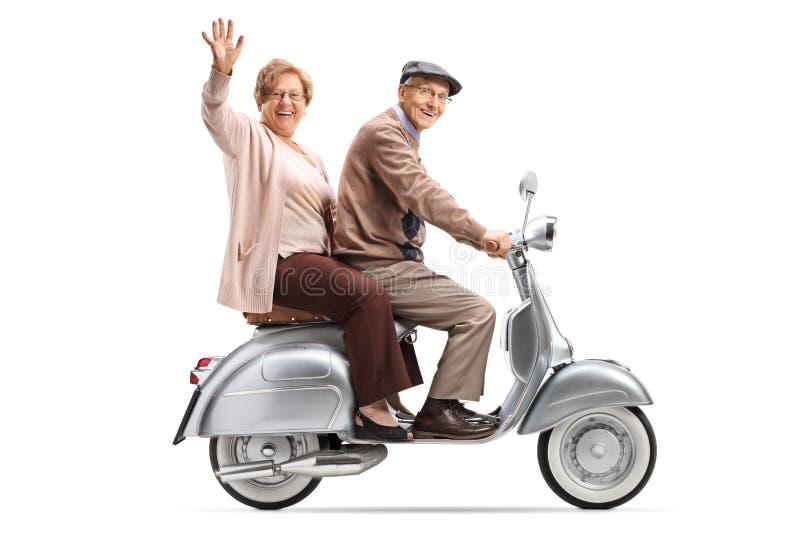 Höga par som rider en sparkcykel och vinka för tappning royaltyfri foto