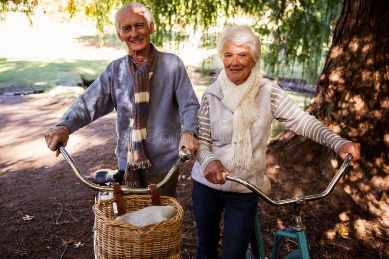 Höga par som rymmer deras cykel royaltyfria bilder
