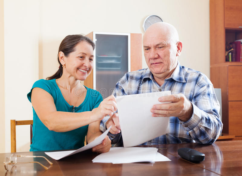 Höga par som rymmer finansiella dokument royaltyfri fotografi