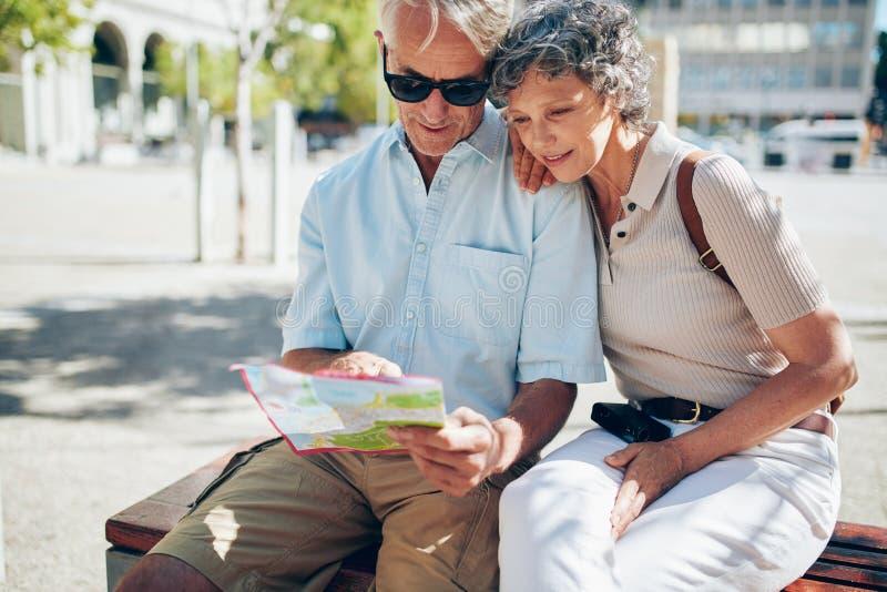 Höga par som söker efter en destination på en stadsöversikt arkivfoton