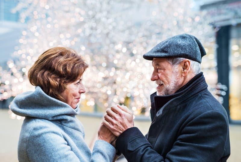Höga par som ser de i shoppingmitt på jultid royaltyfri fotografi