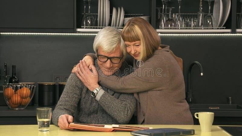 Höga par som ser det gamla fotoalbumet fotografering för bildbyråer