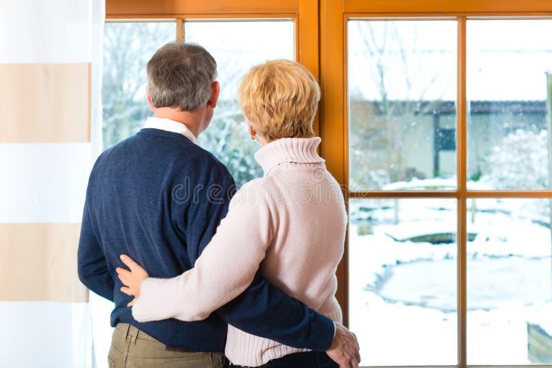 Höga par som ser eller av krama för fönster royaltyfria foton