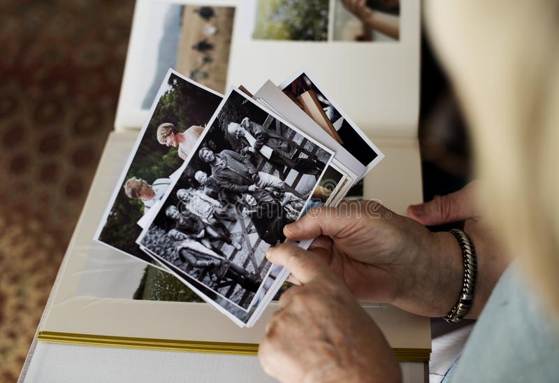 Höga par som ser familjfotoalbumet fotografering för bildbyråer