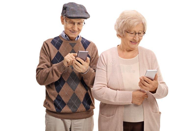 Höga par som ser telefoner fotografering för bildbyråer