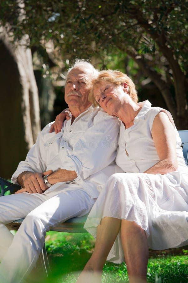 Höga par som sitter i en trädgård royaltyfria bilder