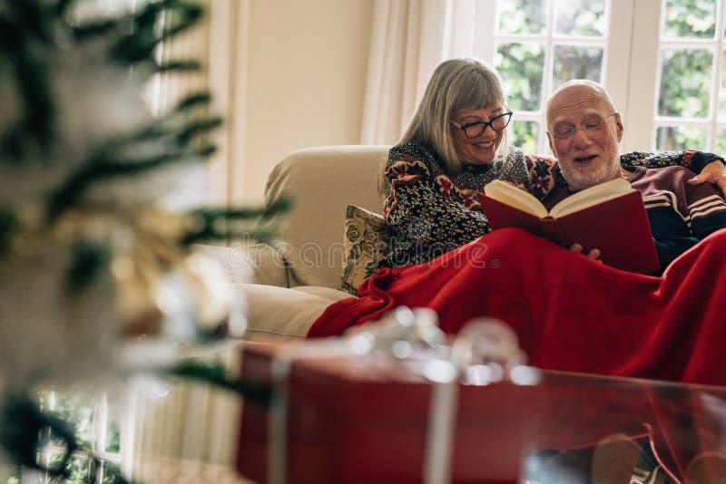 Höga par som sitter på en soffa som tycker om läsa en bok med en gåvaask i förgrunden Le par som tillsammans spenderar tid arkivfoton