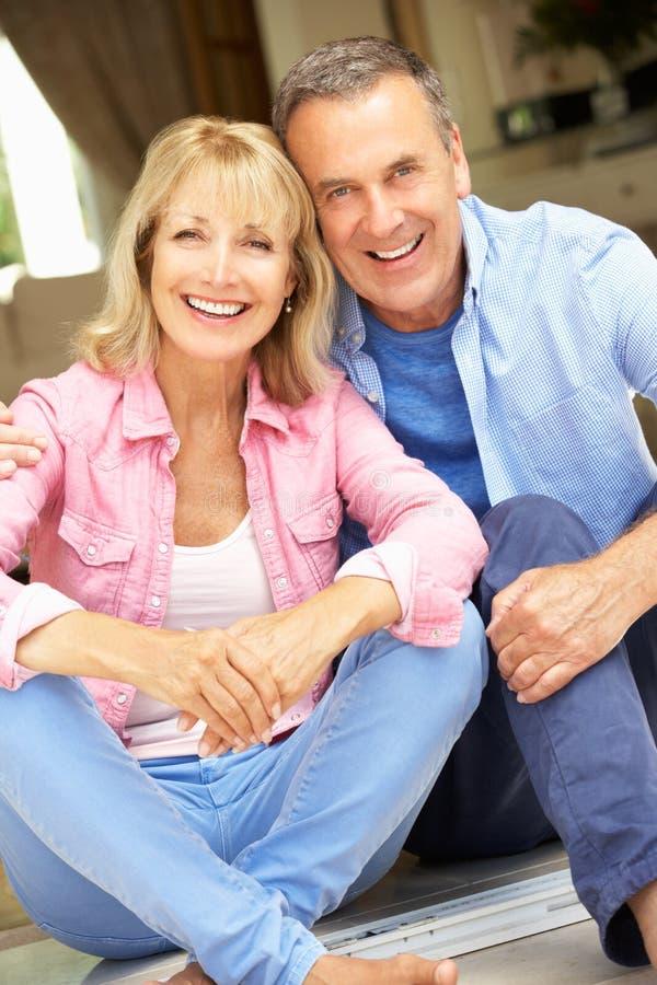 Höga par som sitter utanför hus royaltyfri foto