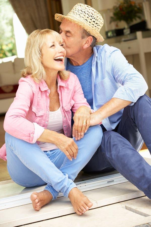 Höga par som sitter utanför hus arkivfoton