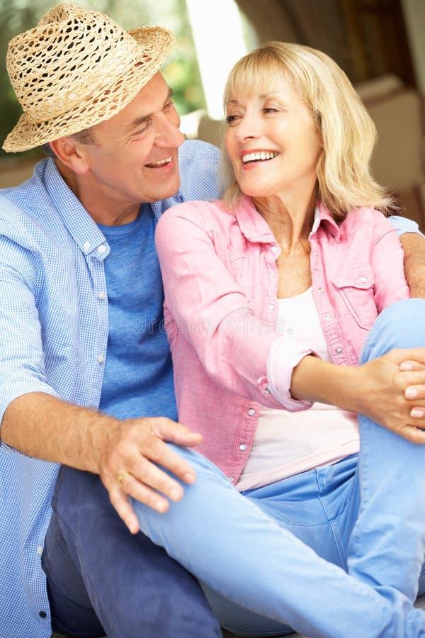 Höga par som sitter utanför hus arkivbilder