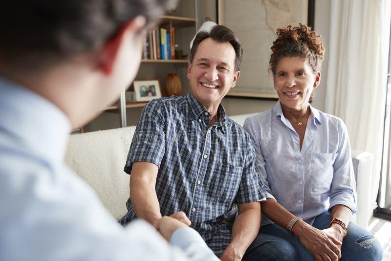 Höga par som skakar händer med den hemmastadda manliga finansiella rådgivaren royaltyfria bilder