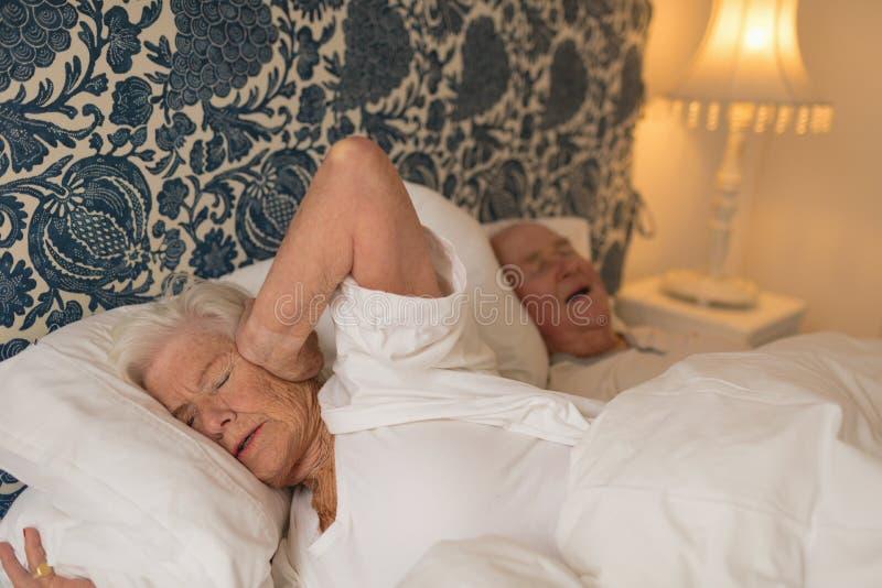 Höga par som sover i sovrum fotografering för bildbyråer