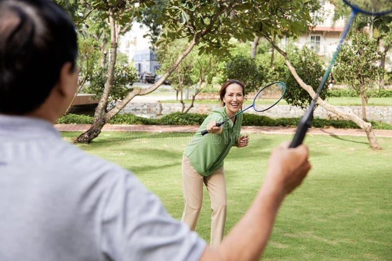 Höga par som spelar badminton arkivbilder
