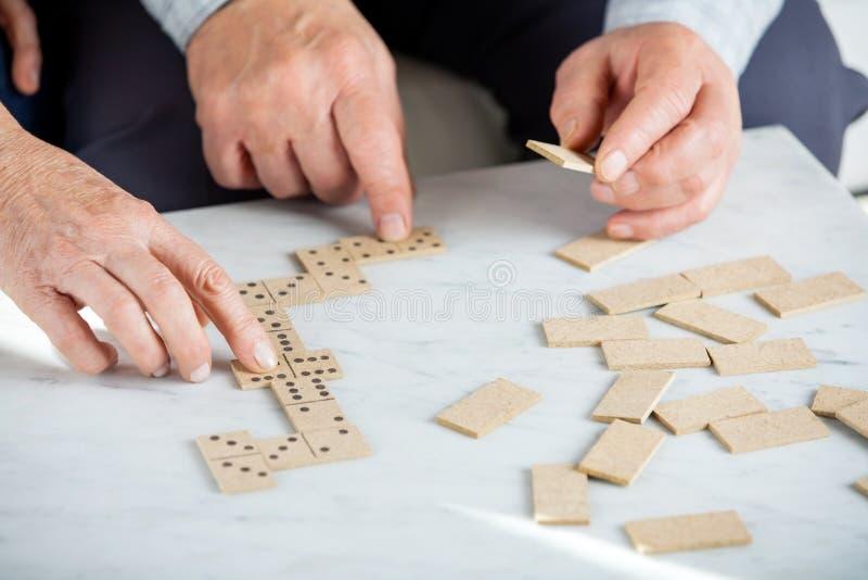 Höga par som spelar domino på tabellen arkivbild