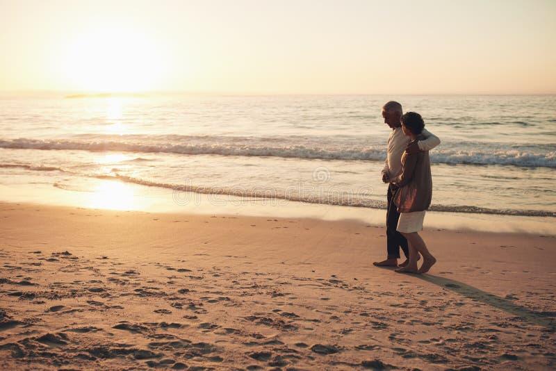 Höga par som strosar på stranden på solnedgången arkivbilder