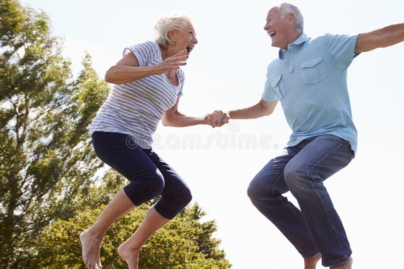 Höga par som studsar på trampolinen i trädgård royaltyfri foto