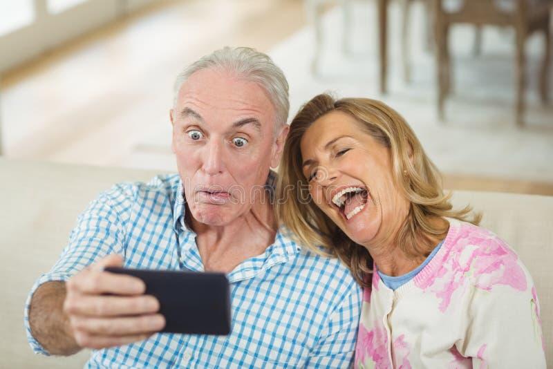 Höga par som tar en selfie på mobiltelefonen i vardagsrum arkivfoto
