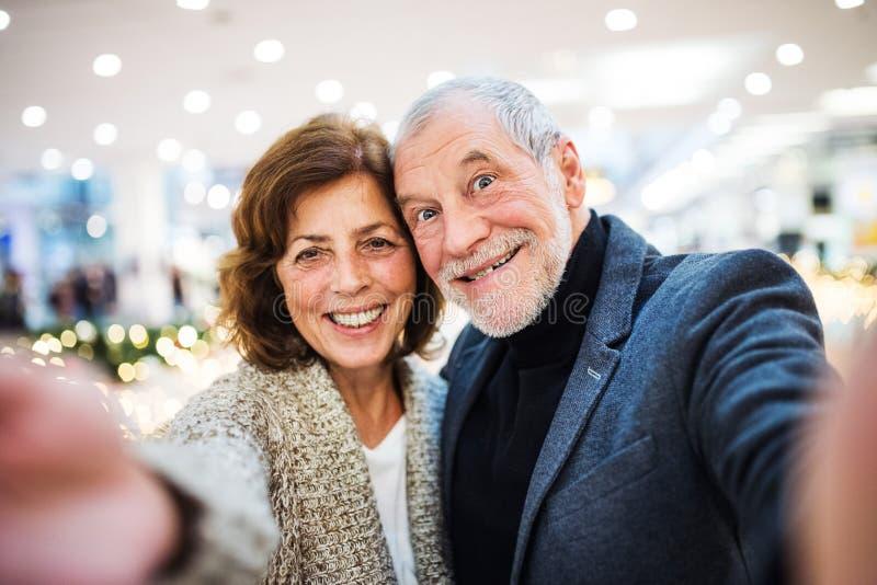 Höga par som tar selfie i köpcentrum på jultid arkivbilder