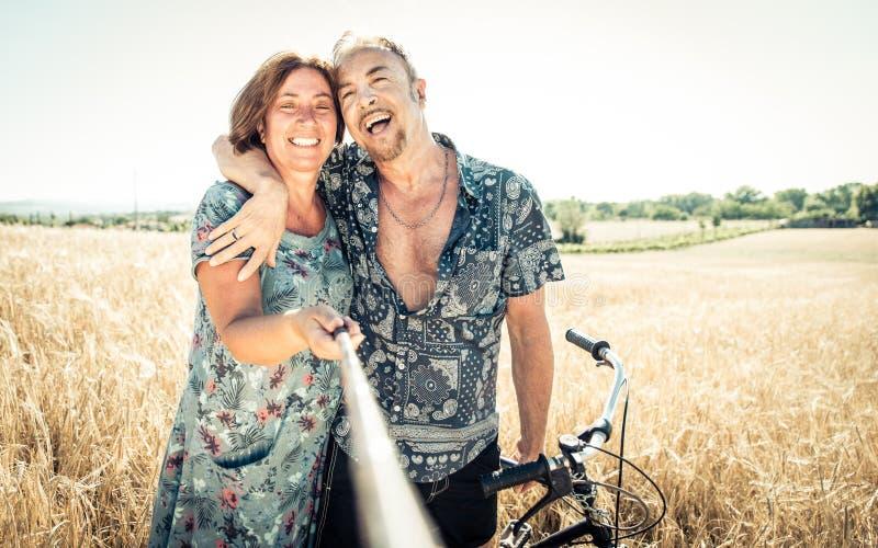Höga par som tar selfie med pinnen royaltyfria foton