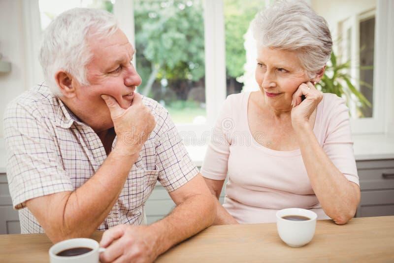 Höga par som till varandra talar, medan ha kaffe arkivbild