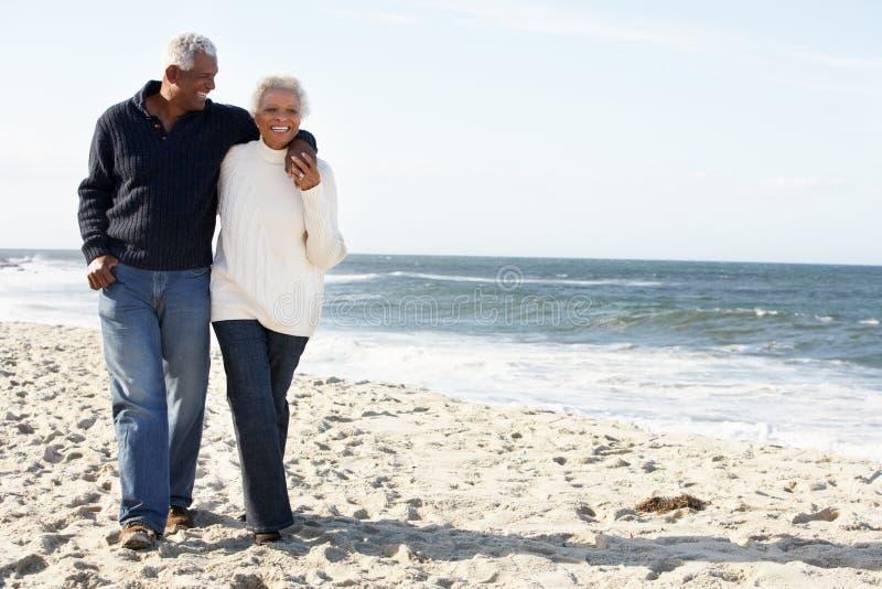 Höga par som tillsammans går längs strand royaltyfria foton