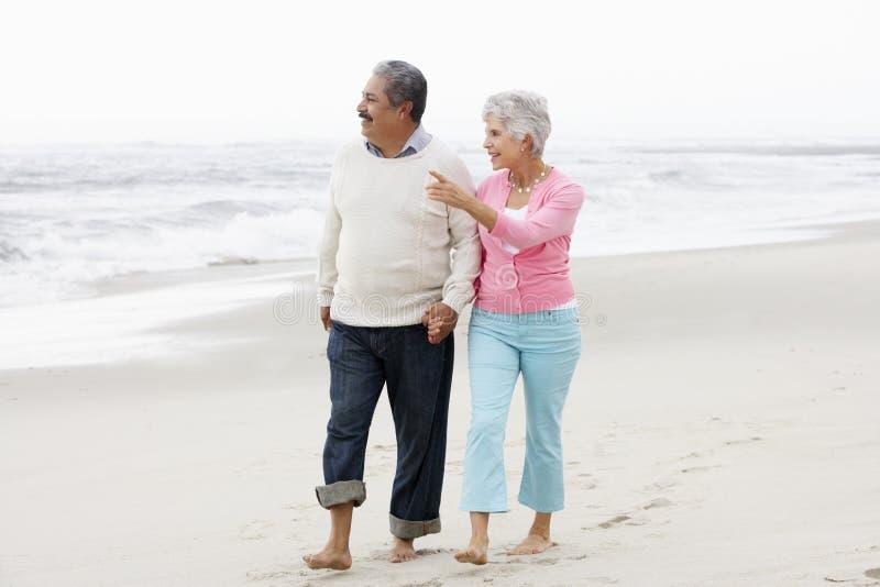 Höga par som tillsammans går längs strand royaltyfri bild