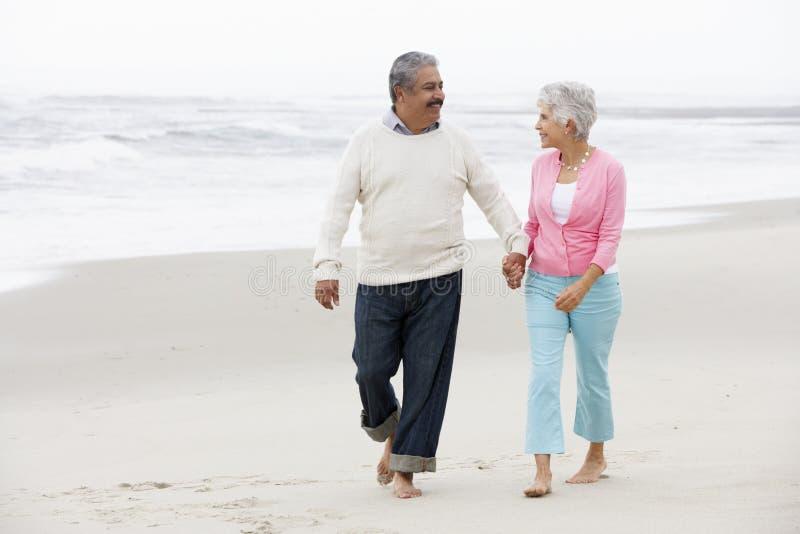 Höga par som tillsammans går längs strand arkivbild