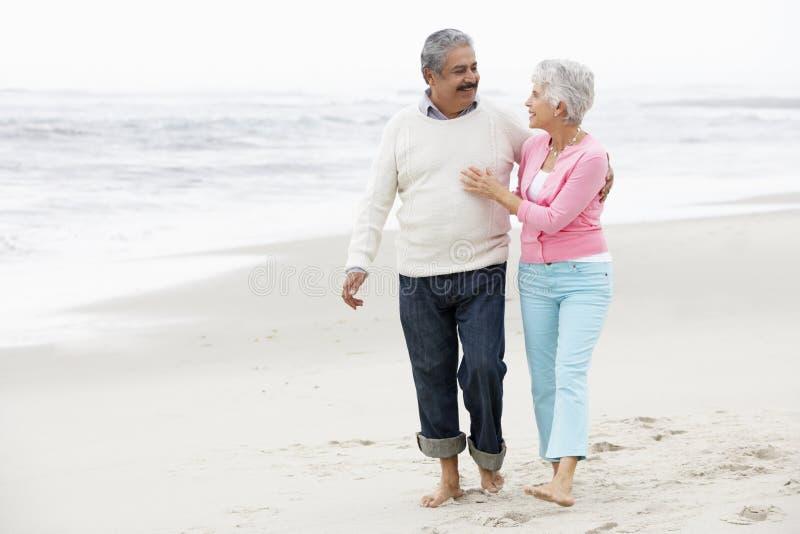 Höga par som tillsammans går längs strand fotografering för bildbyråer