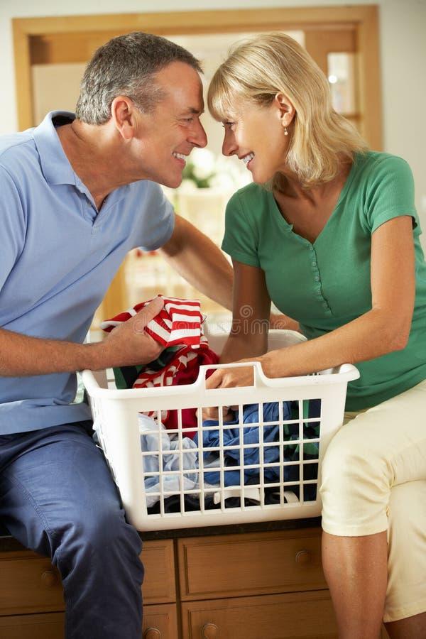 Höga par som tillsammans sorterar tvätterit royaltyfri foto
