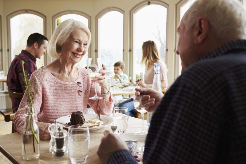 Höga par som tillsammans tycker om efterrätten i restaurang royaltyfri bild