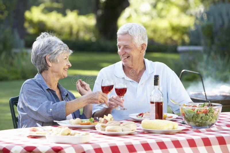 Höga par som tillsammans tycker om grillfesten i trädgård arkivfoto