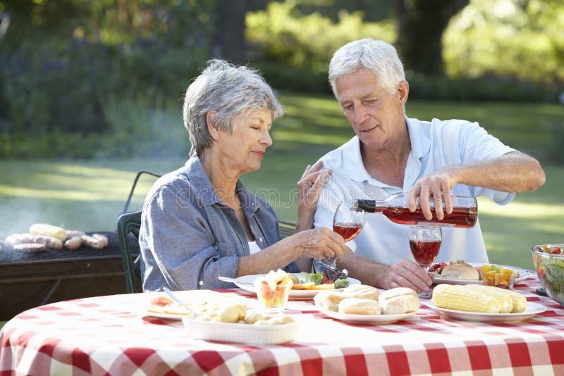 Höga par som tillsammans tycker om grillfesten i trädgård royaltyfri foto