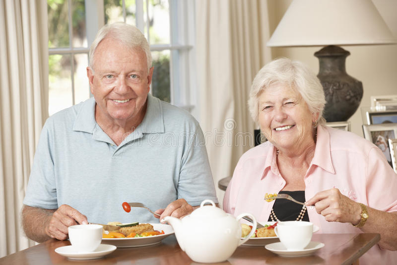 Höga par som tillsammans tycker om mål hemma royaltyfri fotografi