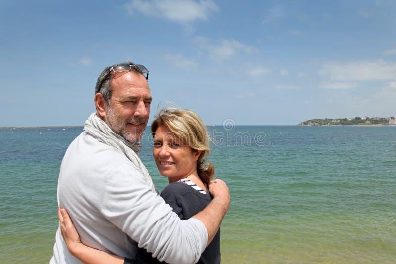 Höga par som tycker om ferier på sjösidan arkivbilder