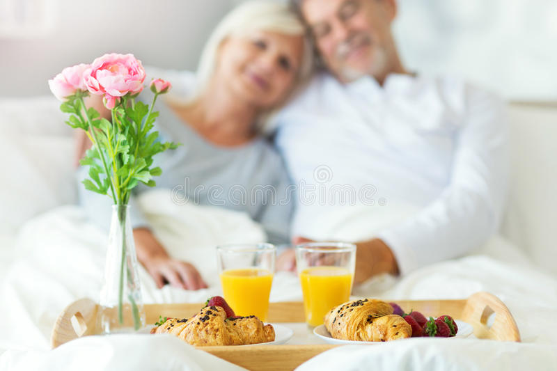 Höga par som tycker om frukosten i säng royaltyfri fotografi