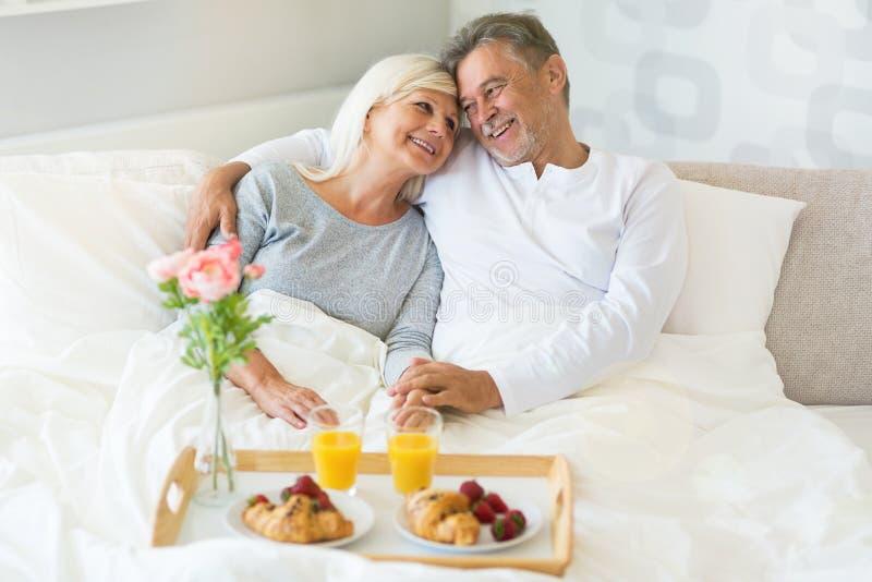Höga par som tycker om frukosten i säng royaltyfria bilder
