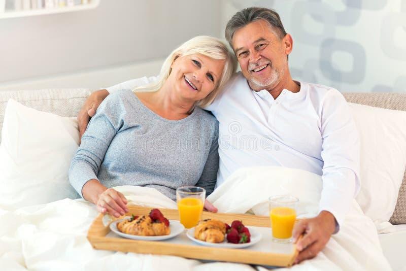 Höga par som tycker om frukosten i säng arkivbild