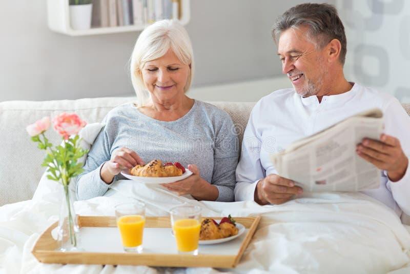 Höga par som tycker om frukosten i säng royaltyfri bild