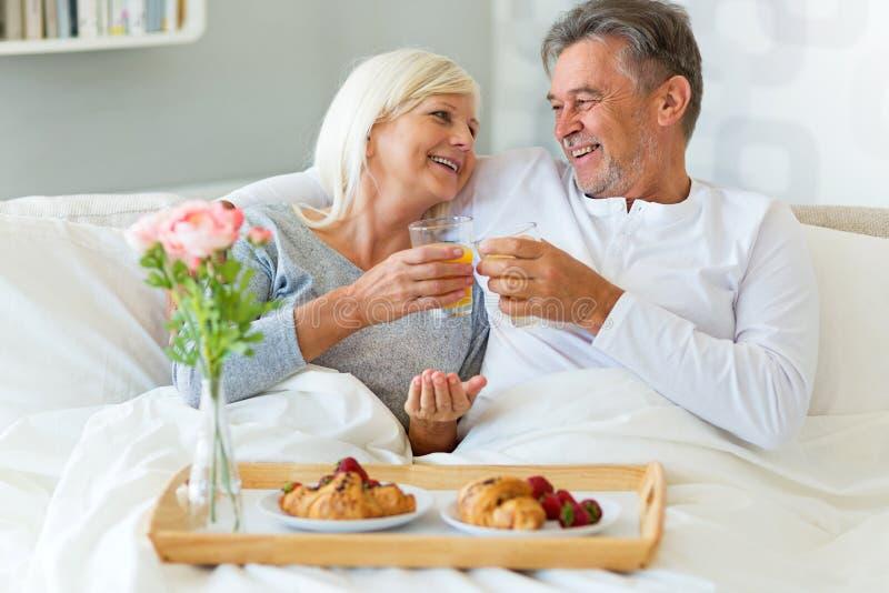 Höga par som tycker om frukosten i säng royaltyfri foto