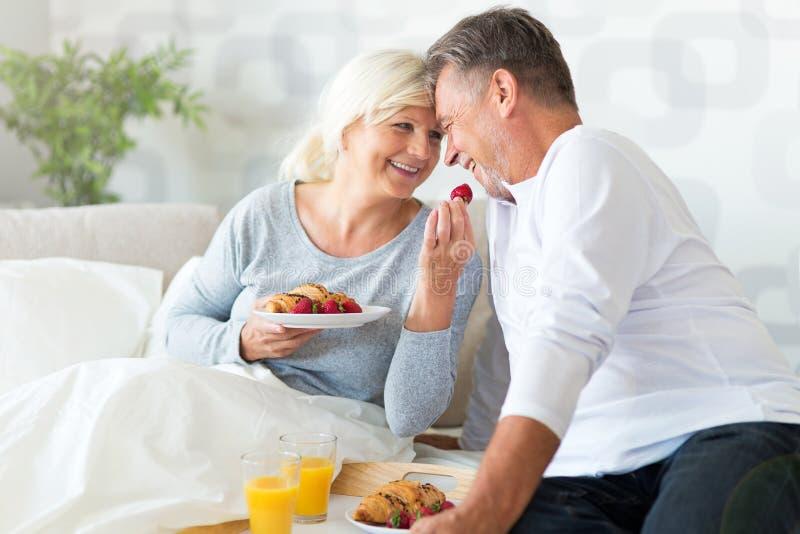 Höga par som tycker om frukosten i säng royaltyfria foton